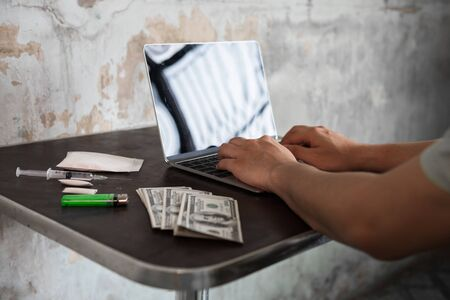 drug sale trafficking over the internet. agent seller man hands using laptop computer to sell narcotic or heroin. Abuse, Crime, and dope illegal concept against law with dirty US money. Black market. Stockfoto