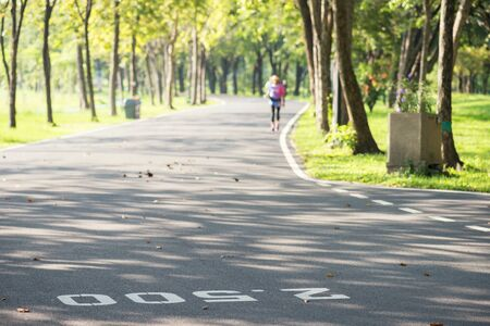 running path of summer park with milestone painted on street with blurred running athlete in morning. Sport and healthy lifestyle.