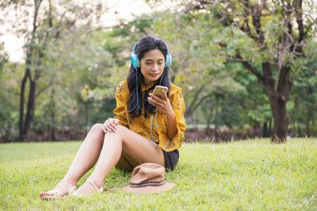 Beautiful Asian Bohemian girl with yellow vintage dress chat and listen online music by smartphone or mobile phone in park. Female hipster play social media, watch video, shop online in garden.