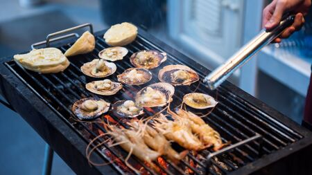 Grilled big sea shrimps, bread with butter, and scallop on grill pan. Seafood barbecue for family party at night.