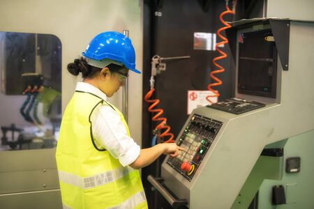 Waist up female engineer worker with hardhat and protection glasses press keyboard button to command automate robot machines in factory workshop. Manufacturing industry with technology. Banque d'images