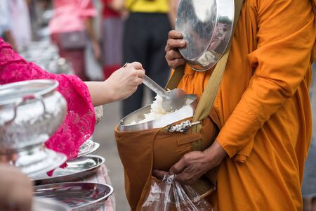 Closeup hands of tourist people offer jasmine rice and food to buddhist monk at early morning at sangkhlaburi district, Kanchanaburi, thailand. Famous travel activity and landmark here.
