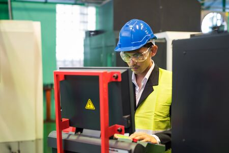 Waist up warehouse manager with hardhat and protection glasses command computer to produce mechanic product by automate robot machine in factory workshop. Manufacturing industry with technology.