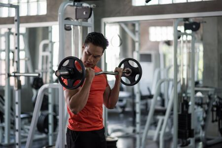 Asian muscular man working out with barbell weights at fitness gym. Muscle man exercising are lifting dumbbells. Bodybuilding, sport, healthy lifestyle concept.
