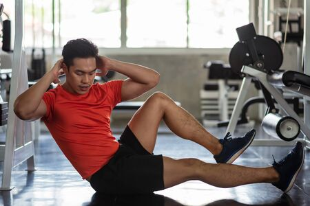 Asian Athlete muscle man doing bicycle crunch to build six packs (upper and lower abs and the obliques) in fitness gym. Bodybuilding, sport, and healthy lifestyle concept. Reklamní fotografie