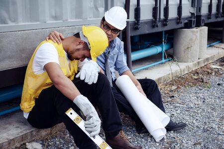 Sad Asian fired arab foreman, 20-30 years old man, cry while senior engineer manager comfort and cheer up at construction site. 2020 bad economy forces to layoff employees. Foto de archivo - 139861684