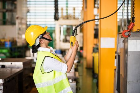 Waist up female worker uses remote control panel for lifting down power trolley crane in factory warehouse. Asian woman controls crane beam in manufacturing facility.