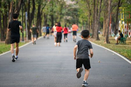 Little boy run fast on park running track with sun light. Bodybuilding, kid sport, and healthy lifestyle concept. Back view.