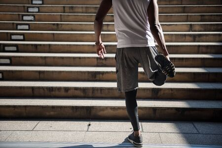 Closeup black african american athlete young man stretching leg and foot before jogging at staircase in urban city. warm up before exercise. Healthy lifestyle with sport activity.