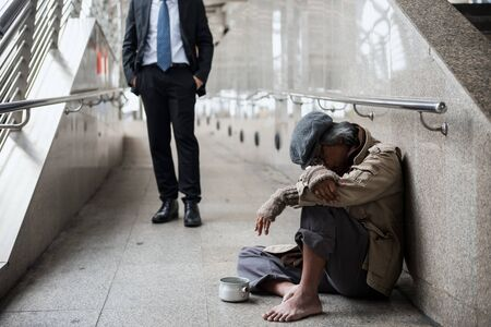 Old beggar or Homeless dirty man sit and sleep on footpath walk of modern city with Kind-hearted businessman background. Jobless in bad world enonomy crisis.