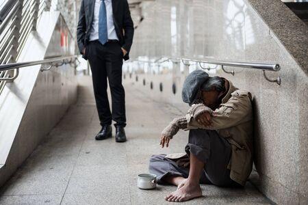 Alter Bettler oder Obdachloser schmutziger Mann sitzen und schlafen auf dem Fußweg der modernen Stadt mit gutherzigem Geschäftsmannhintergrund. Arbeitslos in schlechter Weltwirtschaftskrise.
