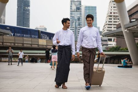 Portrait of Handsome Burmese or Myanmar businessmen with longyi traditional dress pull luggage in Modern city. Smart guys business trip in Bangkok. Work and travel in Foreign country
