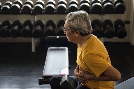 Senior old Asian man with gray hair sit up exercising on bench and having a heart attack with dumbbell equipment at fitness gym. Sport, Insurance, and health care for elderly.