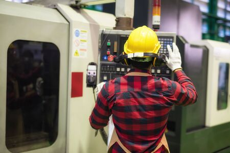 Rear Factory worker with plaid shirt and safety helmet command machine screen and keyboard to produce steel spare part by automatic drilling machine. Heavy industry with high technology.