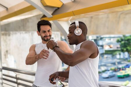 Happy African black man and American bearded friend toast and drink water after running workout in modern city. Bodybuilding and healthy lifetstyle. Lovely LGBT gay couple exercise.