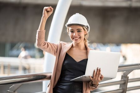 Happy 20s American engineer woman with helmet and coat working on laptop raise hand at urban city. Beautiful female worker celebrate construction project or win bid auction from internet.