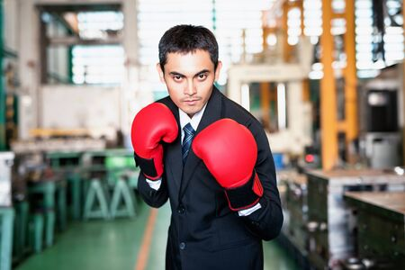 Strong Factory businessman owner with boxing gloves in factory warehouse. Business industry fight agaisnt COVID-19 or coronavirus crisis. Leave without pay, work from home, quarantine, bankruptcy.
