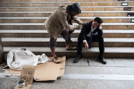Old homeless beggar man cheer up sad businessman in city. Unemployed business man get fired due to covid-19 or coronavirus. Leave without pay, quarantine, work from home, global pandemic disease.