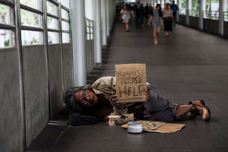 Old Homeless man or beggar carry help plate to ask for money during covid-19 or coronavirus disease. Broke man got less donation due to social distancing, quarantine, work from home.