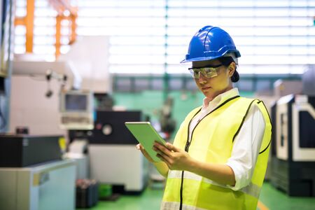 Waist up female worker with hardhat and protection glasses use corporate applciation to check automate robot machines in factory. Manufacture industry with technology. social distancing during covid-19.