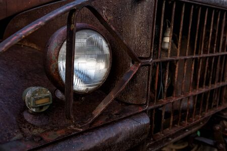 Old broken rusty car. Closeup front light or headlamp of Rust on metal in vintage automobile Imagens