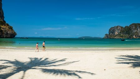 Foreign people walk on Railay Beach with turquoise andaman sea and blue sky in Krabi, Thailand. Holiday maker to relax for summer vacation in Southeast Asia. Famous travel destination in Thai southern.