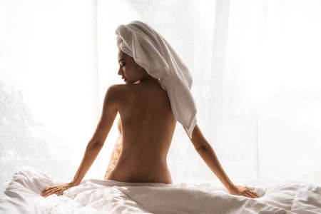 Naked woman wrapped shower towel after taking bath. She sit relax on bed by window. Sexy nude tan girl stay at home due to covid-19 or coronavirus pandemic.  social distancing. Stockfoto