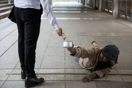 Kind business man with formal suit help and give dollar bill to handicapped beggar male on street begging in winter. Pity old male need money, food, shelter in city.