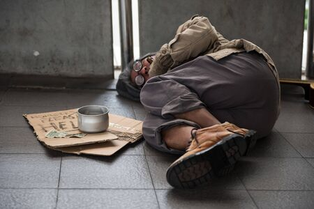 Lifestyle Homeless beggar old man sleep on walkway street in capital city. begging for help and money. Problems of big modern cities. Focus at donated bowl.
