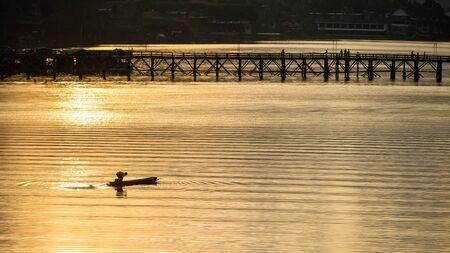 Silhouette fishermen on boat near Mon wooden or Attanusorn bridge at sunrise, Sangkhla Buri, Kanchanaburi, Thailand. village people fishing lifestyle in early morning. Archivio Fotografico - 150270355