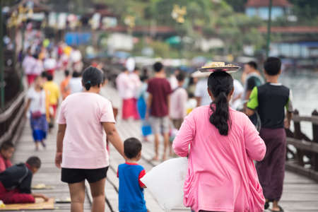 Amazing head balance skills of Female Mon people on Uttamanusorn Bridge in Sangkhla buri, Kanchanaburi province in Thailand. Famous travel destination after covid-19 lock down. Stockfoto