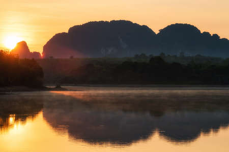 Natural view of beautiful reservoir and Limestone mountains at sunrise with rays, mist, and reflection on water, Nong Thale, Krabi, Thailand. Famous travel destination after covid-19 lock down.