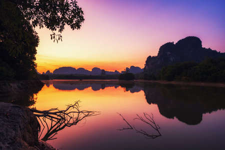 Natural landscape of beautiful reservoir and Limestone mountains at dawn with twilight sky and reflection on water, Nong Thale, Krabi, Thailand. Famous travel destination after covid-19 lock down.