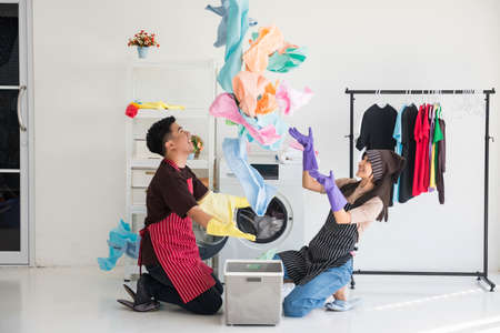 Happy attractive Asian young couple throw clean colorful bath towel fabric after washing on laundry machine. Cheerful wife and husband on housework duty in weekend.