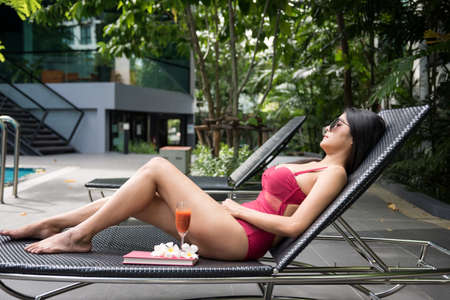 Portrait of sexy Asian beautiful woman in red swimsuit and sunglasses  sleep or nap on bed chair to get suntan near swimming pool. Female relax in luxury hotel for summer holiday or vacation.