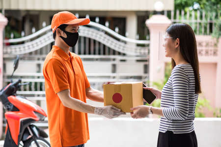 Courier delivery with face mask and glove in orange uniform giving cardboard parcel to Asian smiling woman with face shield. online packaging send to home by motorbike. COVID-19 pandemic. New normal
