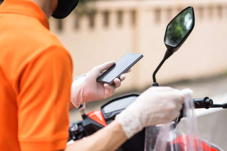 Courier deliveryman with face mask and glove on motorbike or motorcycle check customer location by smartphone. New normal of food delivery business during covid19 or coronavirus pandemic concept.