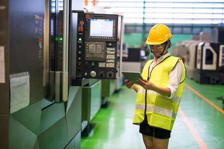 Waist up female worker with hardhat and protection glasses check corporate app in tablet to control automate lathe robot machines in factory. Manufacture industry with technology to inspect or audit.