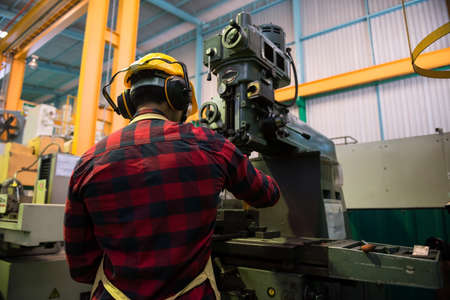 Rear Factory specialist worker with helmet and glassed work on milling machine. Heavy industry with automate machinery background with copy space for text.