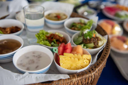 Food set for offering to Buddhist monks in Thailand. Main course, dessert, and fruit on basket tray.