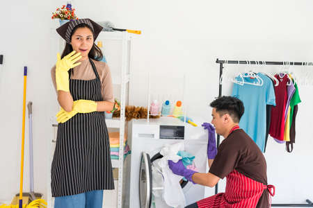 Asian young idle housewife laughing to see her husband or boyfriend to laundry by himself. Housework to man while lazy smiling wife control his work.
