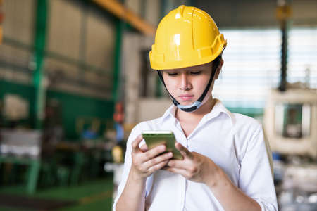 Factory engineer with hardhat check corporate app and chat on smartphone in factory warehouse. Manufacturing industry and technology. Industry with inventory concept.