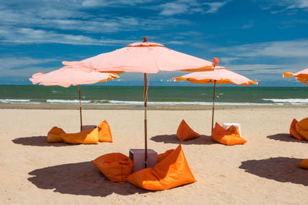 view of beautiful summer beach and sea with orange soft beanbag seat and parasol umbrella on sand at Cha-Am, Petchburi, Thailand. holidays travel and tropical tourist destination concept