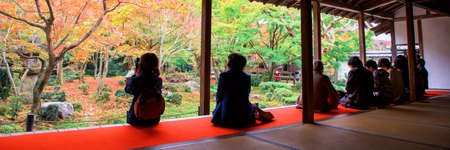 Tourist people sit in building to enjoy view of Autumn foliage maple colors in Enkoji temple Japanese Garden, Kyoto, Japan. Travel, landmark. Header or banner travel background.