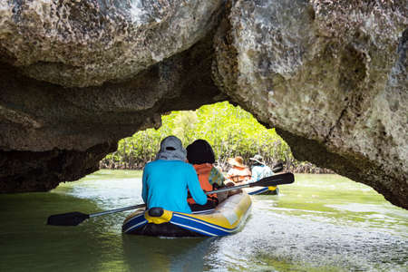 Tourist and sailor canoeing through Tham Lod (small grotto cave) of Karst formations to visit lagoon and mangrove tree forest swamp in Phang Nga bay, Thailand. Famous travel destinaton in summer.
