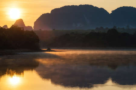 Sunrise landscape of beautiful lake swamp with motion mist and Limestone mountains in morning, Nong Thale, Krabi, Thailand. Famous travel destination in south of Thai.