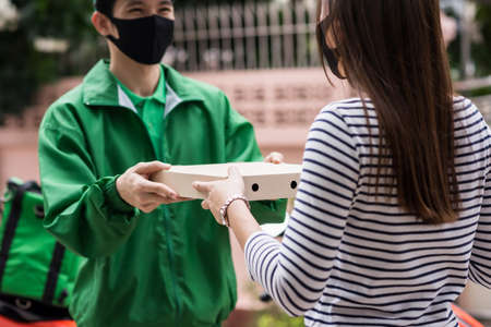 Female customer with face mask take pizza food order from deliveryman in green jacket uniform near motorbike. Health protection for covid-19 pandemic. new normal to eat from home. 免版税图像