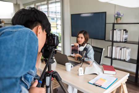Video or professional digital camera man prepare to shoot live streaming of beautiful attractive Asian woman blogger podcaster with studio lighting. broadcasting for online journal or website content.