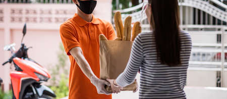 deliveryman with face mask and gloves in orange uniform give bag of bread food deliver to female costumer wirh face shield in front of home. delivery by motorcycle during covid19.