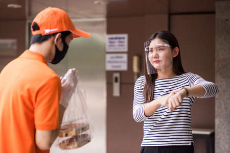 Angry Asian starving woman in face shield show watch to complain about delivering food late. Courier delivery man with face mask regret or sorry. Furious girl wait food at office with covid19 protect 免版税图像